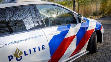 Een foto van een politieauto, op de zijkant boven het logo van de politie staat 'waakzaam en dienstbaar'. Agent vliegt uit de bocht en doet discriminerende uitspraak.