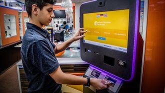 Een klant in een belwinkel in Rotterdam wisselt via een scherm euro's om voor bitcoins. Foto: ANP | Robin Utrecht