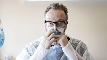 Op deze foto zie je een arts die een patients helpt, met beschermende kleding