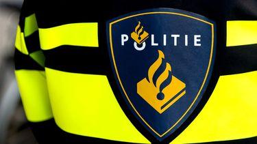 Een foto van een politielogo op de rug van een agent