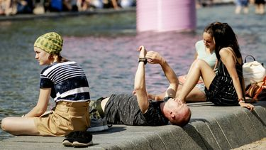 Een foto van drie jongeren op een kade in de zon