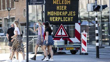 Op deze foto is een bord te zien met daarop 'welkom, hier mondkapjes verplicht' in Rotterdam.