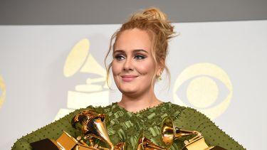 Een foto waarop zangeres Adele te zien is met muziekprijzen in haar armen.