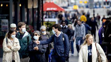 Een foto van mensen met een mondkapje; die maken deel uit van de nieuwe coronamaatregelen