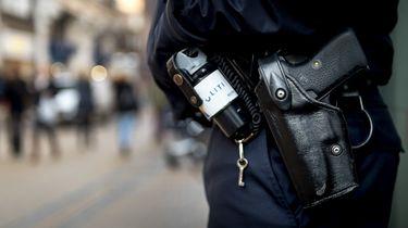 Op deze foto is de uitrusting van een politieagent te zien: pepperspray en een dienstwapen.