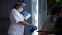 Op deze foto is een vrouw te zien die de handen van een ander met een desinfectiespray bespuit.