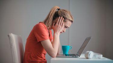 vrouw achter laptop is slachtoffer van pesten op het werk