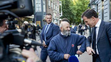 Een foto van Mark Rutte die met een elleboogje een voorbijganger groet.
