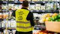Een foto van een medewerker van een supermarkt in een geel hesje