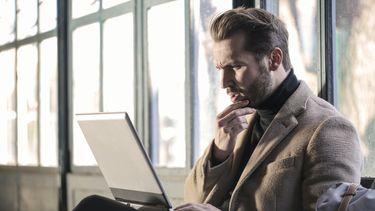 man wil carriereswitch maken en doet onderzoek op laptop