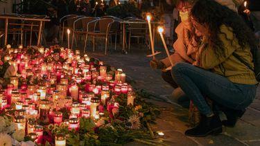 Op deze foto zijn mensen te zien bij een gedenkplek voor de aanslag in Wenen.