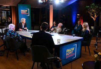 Een foto van de setting van Pauw Komt Binnen met meerdere mensen om tafel