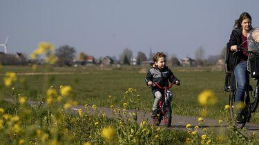 Moeder en kindje fietsen door de wei.