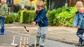 Op de foto kinderen die een ringspel spelen, buiten op straat.