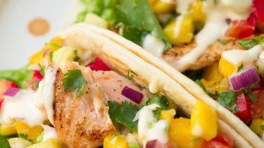 Op deze foto zie je taco's met zalm en avocado-mangosalsa