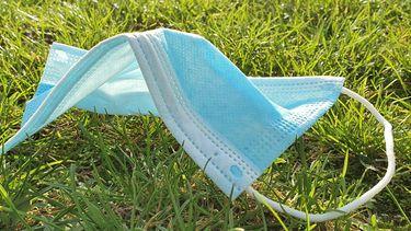 Een foto van een mondkapje in het gras