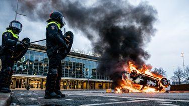 Een foto van de rellen in Eindhoven met een brandende auto