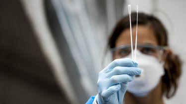Een foto van een medewerker in de zorg met een coronatest