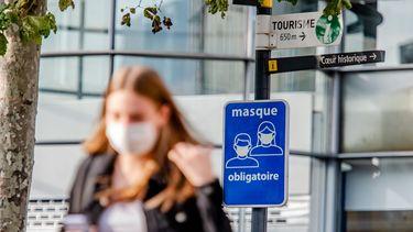 Een foto van iemand in België met een mondkapje op. In de achtergrond staat een bord met 'masker verplicht', in het Frans.
