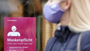 Op deze foto is een bord te zien met 'Maskenplficht' erop, daarvoor staat iemand met een mondkapje op.