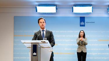 Premier Mark Rutte (l) en minister Hugo de Jonge. Achter hen de doventolk.