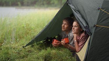 Een foto van een jong stel dat samen uit een tent kijkt op de groene oever van een meer. Ze hebben oranje kampeerbekers vast. Staatsbosbeheer sluit alle wildkampeerterreinen.