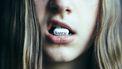 Foto van een meisje met een pil in haar moond