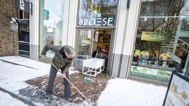 Een foto van een eigenaar van een van de winkels die weer opengaat, hij veegt zijn stoep schoon