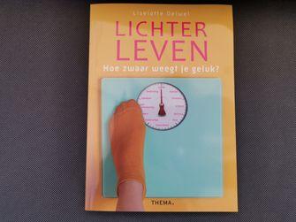 Een foto waarop de cover van het boek Lichter leven. Hoe zwaar weegt je geluk? te zien is. Op de cover staat een weegschaal met woorden zoals 'liefde', 'familie' en 'genieten'.