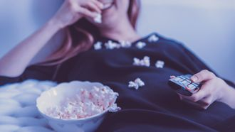 Een vrouw met een afstandsbediening kijkt televisie met popcorn.