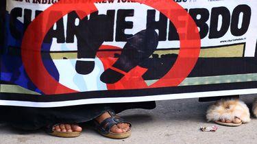 Op deze foto is een spandoek te zien met daarop Charlie Hebdo met een kruis erdoor.