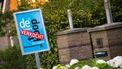 Een foto van een te koop bord in de tuin voor een oprit, op het bord zit een rode 'verkocht' stikker.