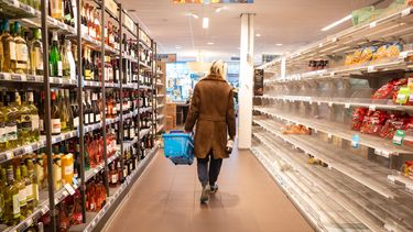 Een foto van een persoon die helemaal alleen in een supermarkt loopt.
