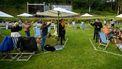 Op deze foto zijn mensen bij een festival te zien, er staan stoeltjes in een afgeplakt vak, zodat er afstand gehouden kan worden.
