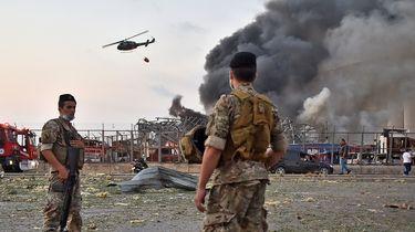 Op deze foto zie je twee Libanese soldaten kijken naar hoe eenhelikopter bezig is de brand te blussen welke ontstaan is door de explosie