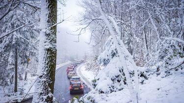 Sneeuw bij Drielandenpunt, auto's staan in de file.