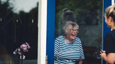 Op de foto een jongere die boter kaas en eieren speelt met een blijde oudere mevrouw