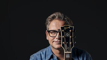 Een foto van Guus Meeuwis met een gitaarhals voor zijn gezicht