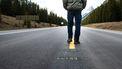 Een man loopt midden op de weg.