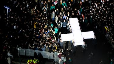 Een foto van een verlicht kruis dat door mensen richting het Passion-podium wordt getild.