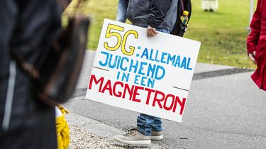 Een foto van iemand bij een 5G demonstratie met een bord waarop staat: 5G: allemaal juichend in een magnetron