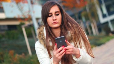 Een jonge vrouw kijkt op haar smartphone. Foto: Pixabay