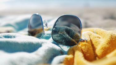 Op deze foto zie je een zonnebril op een stapeltje handdoeken liggen op het strand