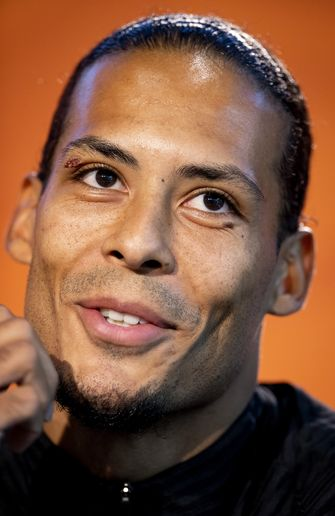 Een foto van een vrolijke Virgil van Dijk bij de persconferentie