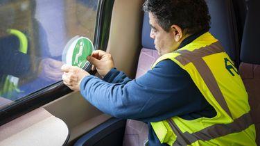 Een foto van een NS-medewerker die een sticker op een treinraam plakt, een sticker die aangeeft dat je op die plek mag zitten