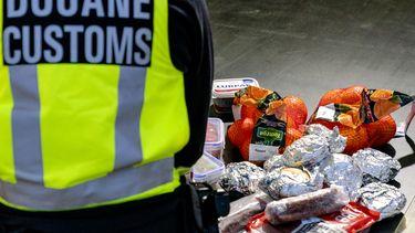 Een douanier met ingenomen voedingsmiddelen van Britten, door de brexit mag het niet meer mee.