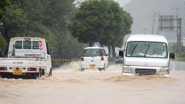 Auto's rijden door een overstroomd gebied in Yatsushiro, Japan.