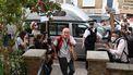 Een foto van Dominic Cummings die tussen fotografen en protestanten door naar zijn huis loopt