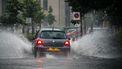 Een foto van een auto die door enorme plassen water rijdt neerslag