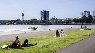Een foto van mensen die aan de waterkant genieten van een warme dag in Rotterdam